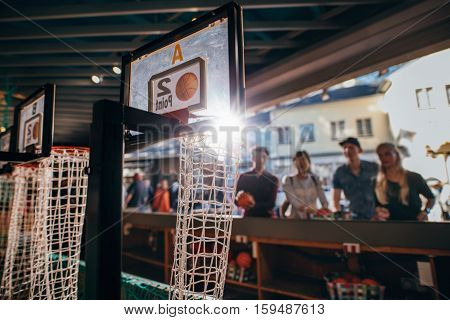 Young People Playing Basketball Game At Amusement Park