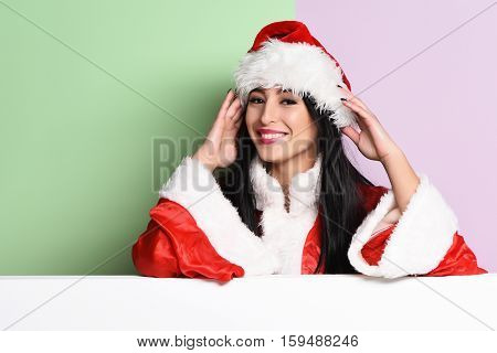 pretty cute sexy santa girl or smiling brunette woman in red sweater and christmas or xmas hat on purple green studio background