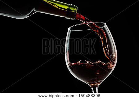 Grape wine poured from bottle into wine glass from glass on black background