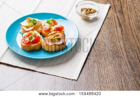 Traditional Italian antipasti bruschetta with tomato, cheese and bacon