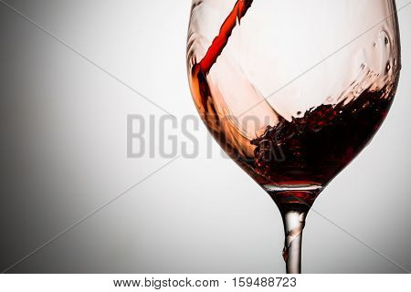 In glass on thin stalk poured stream of red wine