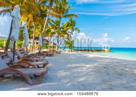 Beach chairs with umbrella at Maldives island with white sandy beach and sea