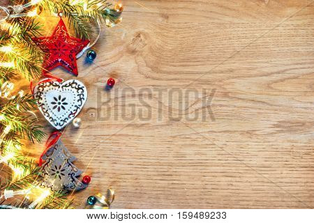 Merry X-mas! Christmas holiday background. Decorated fir tree with lights on wooden board. Top view