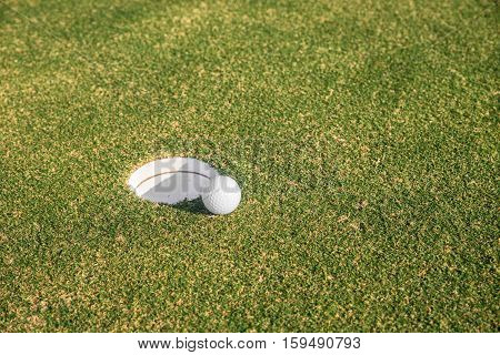 Golf ball sits at the lip of the hole on the putting green. Golf sport concept