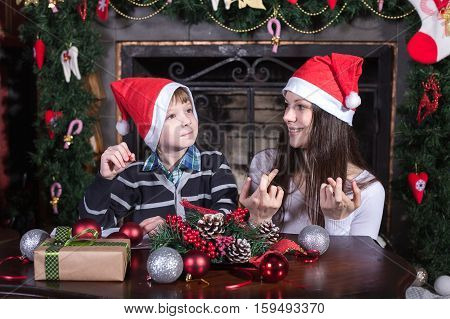mother and son writing letter to Santa indoor near christmass tree