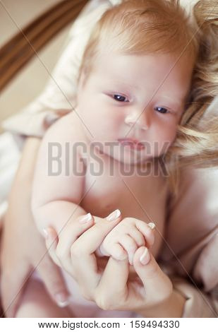 Close-up Portrait Of Baby Lying On Mother Hand. Mom And Child Concept. One Month Infant
