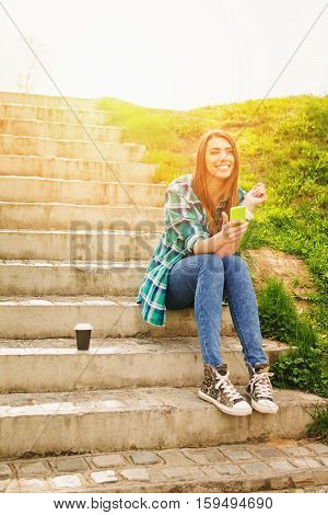 Portrait of cute happy blonde teenage girl in park on sunny day, wearing casual clothes, using smart phone, texting, with cup of takeaway coffee next to her. Retouched, vibrant colors, back light.