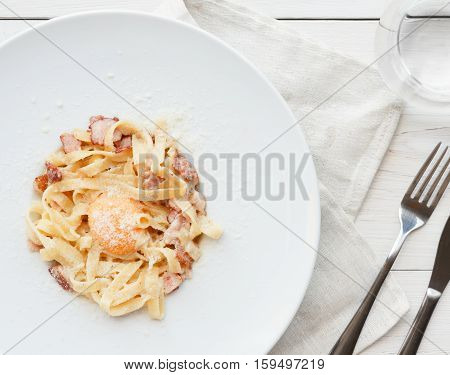 Traditional italian carbonara pasta with bacon, egg yolk and parmesan decorated with basil on white round plate. Restaurant food closeup, top view.