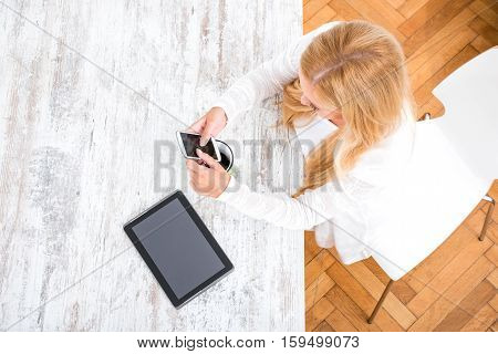 A beautiful young blond woman siting at the table having a coffee and talking on the phone