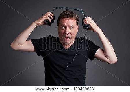 A middle age man holding away the headphone from his ears while suffering