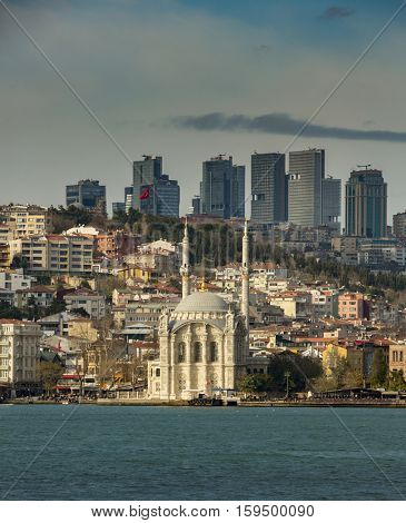 Famous Mecidiye Mosque in Ortakoy and Istanbul business district in the background