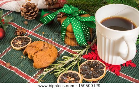 Cookies Tied With Green Ribbon And Coffee With Christmas Decoration, On Wooden Surface.