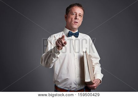 Middle age man looking and pointing in the camera in a shirt and a bowtie