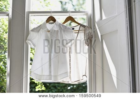 Blouses on hangers at domestic window