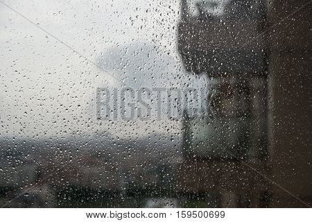 rain drops on glass with a blur apartment at background