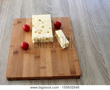 two pieces of cheese Cheese with Cherry tomatoes on a cutting board food