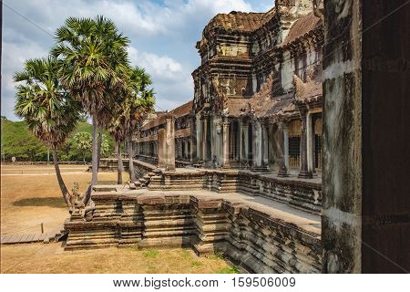 Ancient ruins of temple complex Angkor Wat surrounded by palm trees, Siem Reap, Cambodia.