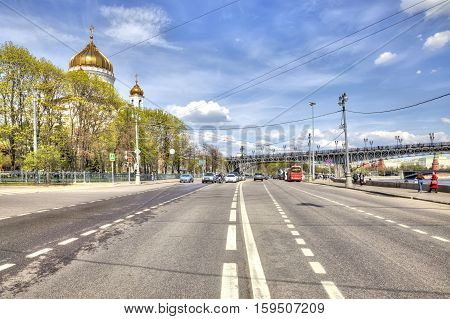 MOSCOW RUSSIA - May 02.2016: Prechistenskaya embankment. Road along the river Moskva next to Cathedral of Christ the Saviour toward Kremlin