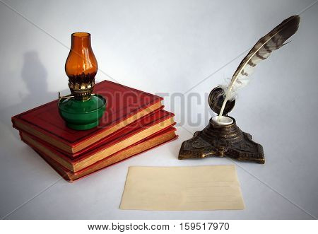 Blank paper card oil lamp and inkwell with a quill pen as a concept of writing letters and greetings on holidays. Photos with vignetting.
