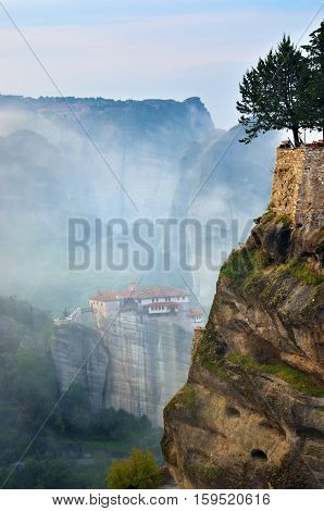 Meteora monasteries. Beautiful view on the rocks and the Holy Monastery Roussanov placed on the edge of high rock before sunrise Kastraki Greece