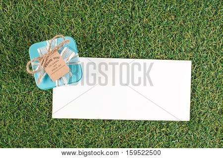 The gift box with tag on the grass ground