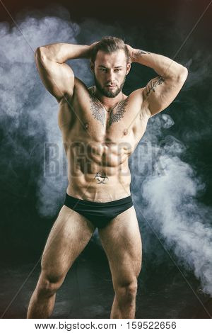 Handsome shirtless muscular man in briefs, standing, on dark smoky background