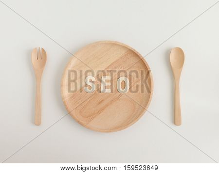 SEO ready meal, text seo on the wooden plate with spoon and fork , top view
