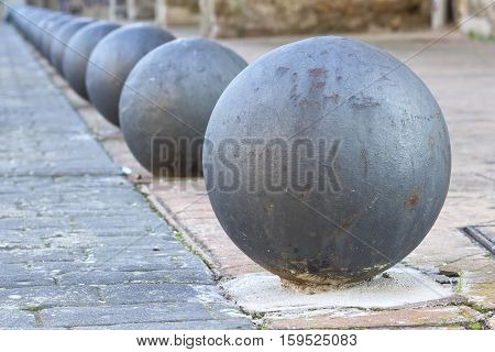Line of grey rusty round bollards in perspective.