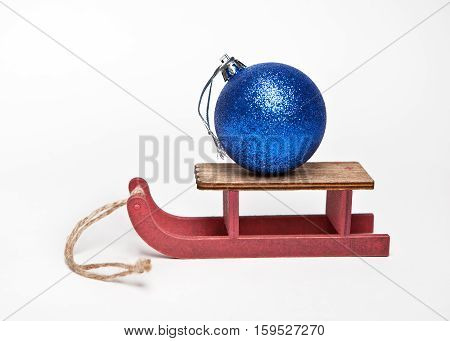 Blue Christmas ball on a wooden sled on white background
