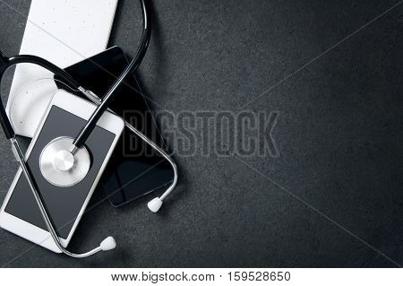 Smartphones and a stethoscope on the desk. Concept of diagnose faults in the phone