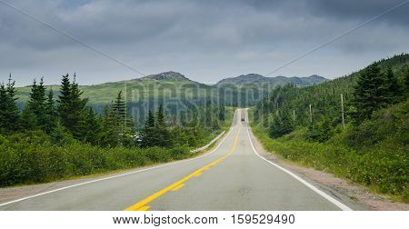 Newfoundland highway in overcast skies.  Lone car goes down the road.  Coastal highways in foothills and valley ranges of Newfoundland.