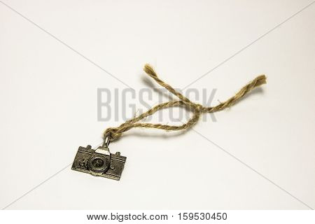 Keychain in the form of retro camera tethered to a beautiful brown cord on a white background