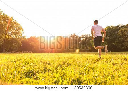 A handsome young man running on a summer evening in the sunset in a park.