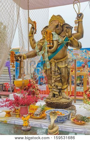 Bangkok, Thailand - January 8, 2016: The old Ganesha statue is set for people to worship in Wat Arun Bangkok Thailand. Chains of Thai Paper Money Hung offering in Buddhist Temple for Good Luck