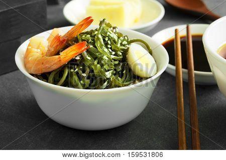 Delicious fresh seaweed salad with quail egg and seasame. Close up