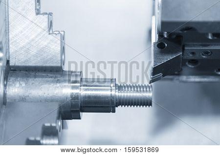 Closeup of the CNC lath machine (Turning machine) while cutting the screw thread in light blue scene.