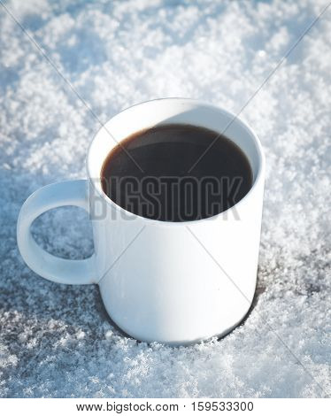 one mug of hot coffee in the winter on a snow-covered wooden table in nature