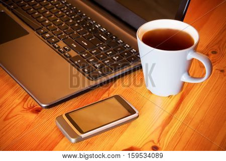 Smartphone laptop and tea cup on wooden table. Selective focus