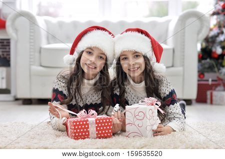 Portrait of cute twin girls with Christmas presents smiling and looking at the camera