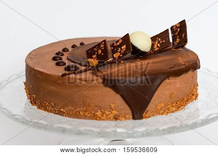 Chocolate ake on a glass stand photographed against a white background closeup