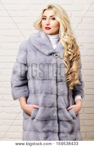 young fashionable sexy pretty woman with beautiful long curly blonde hair in waist coat of grey fur and fashion makeup on brick wall studio background