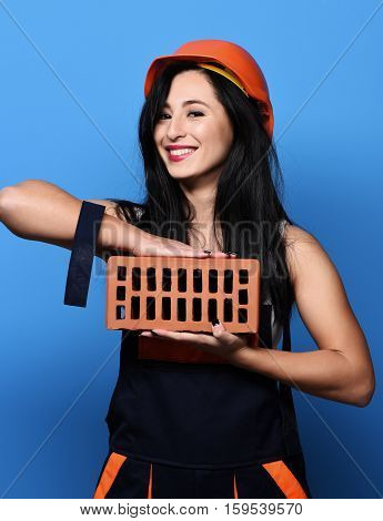 pretty cute sexy builder girl or smiling brunette woman in uniform and hard hat or helmet holding brick on blue studio background