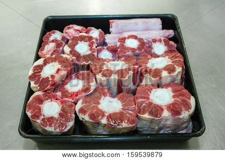Fresh Raw Beef Oxtail Meat cut ready to cook. Beef oxtail on black bowl Fresh raw oxtails (ox tails) cut
