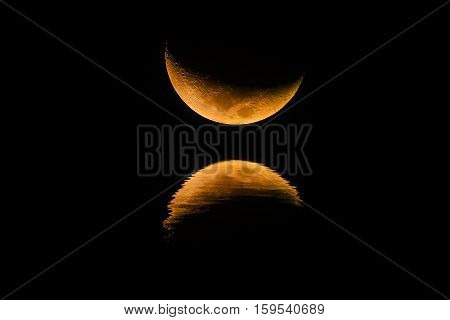 The crescent moon and shadows in the water.