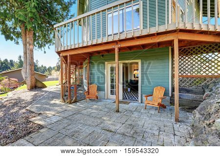 Backyard View Of Waterfront Home With Green Siding