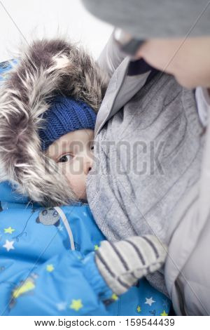 Breast-feeding in unusual circumstance. Mother feed baby outside in cold winter weather. Boy suckles despite on weather happy and calm.