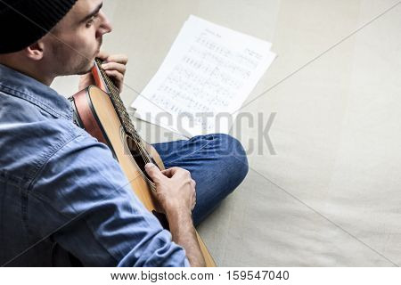 Playing a folk song on acoustic guitar at home. Man in jeans clothes composes music sitting in bedroom