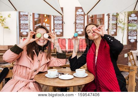 Two funny young women sitting and having fun together in outdoor cafe