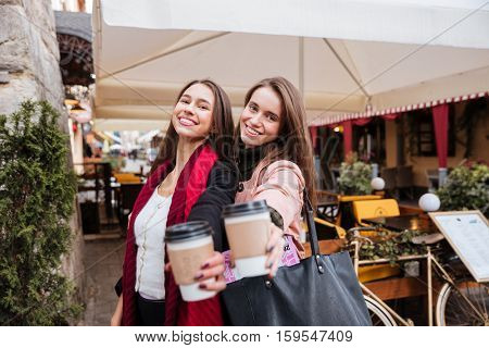 Two happy cute young women holding and giving to you cups of coffee in old town