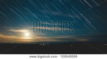 Star trails in the night sky. Moon and clouds in long exposure shot of stars streaking down the sky.